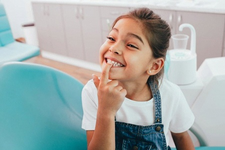 little girl pointing to her teeth at checkup and cleaning for kids in Kaufman