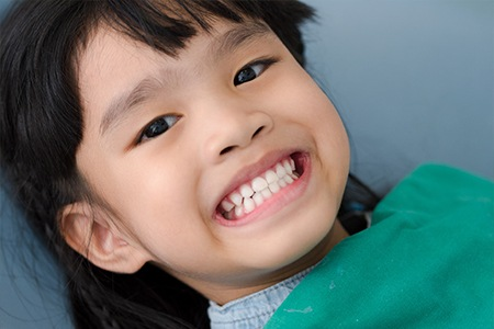 Child in dental chair smiling