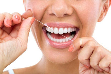 A woman flossing her smile.