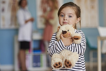 Little girl holding stuffed bear
